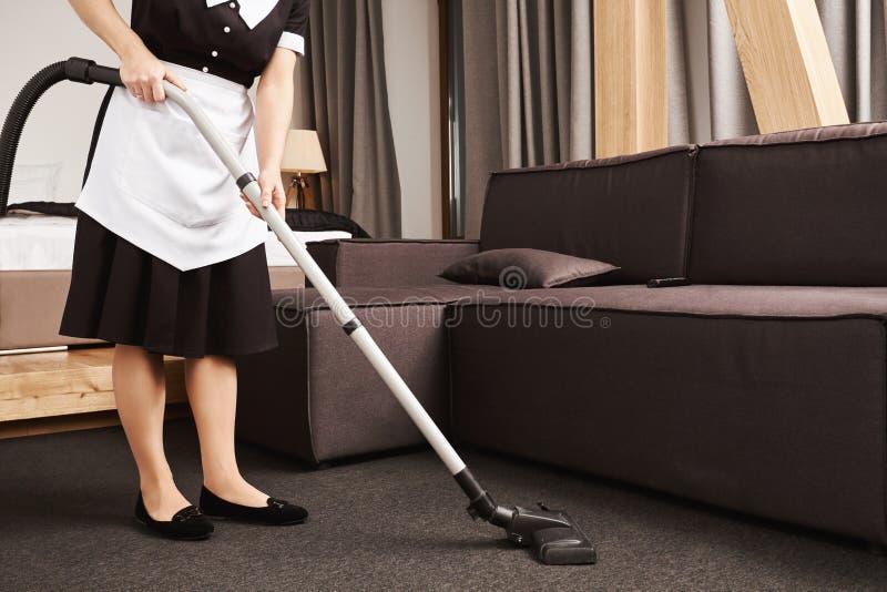 干净的房子为生产力是关键的 佣人播种的射击在工作,有吸尘器的清洗的客厅期间的 免版税库存照片