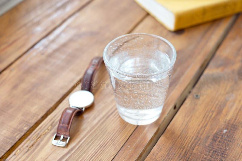 干净的杯在一张木桌上的水,当读时著作时钟提醒您通常采取水一种健康生活方式 库存照片