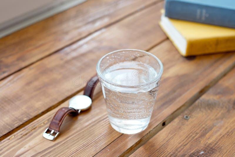 干净的杯在一张木桌上的水,当读时著作时钟提醒您通常采取水一种健康生活方式 免版税图库摄影