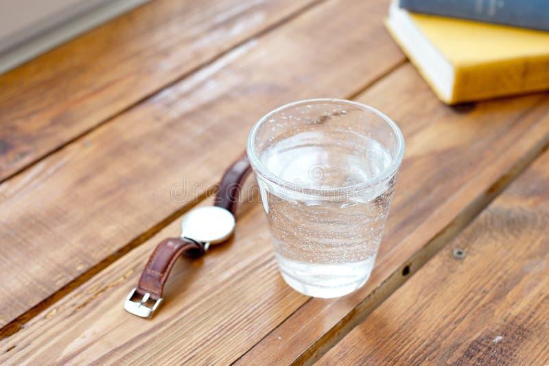 干净的杯在一张木桌上的水,当读时著作时钟提醒您通常采取水一种健康生活方式 库存图片