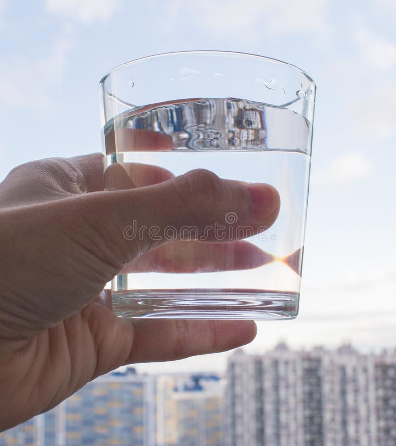 干净的杯水在手中在蓝天背景 图库摄影