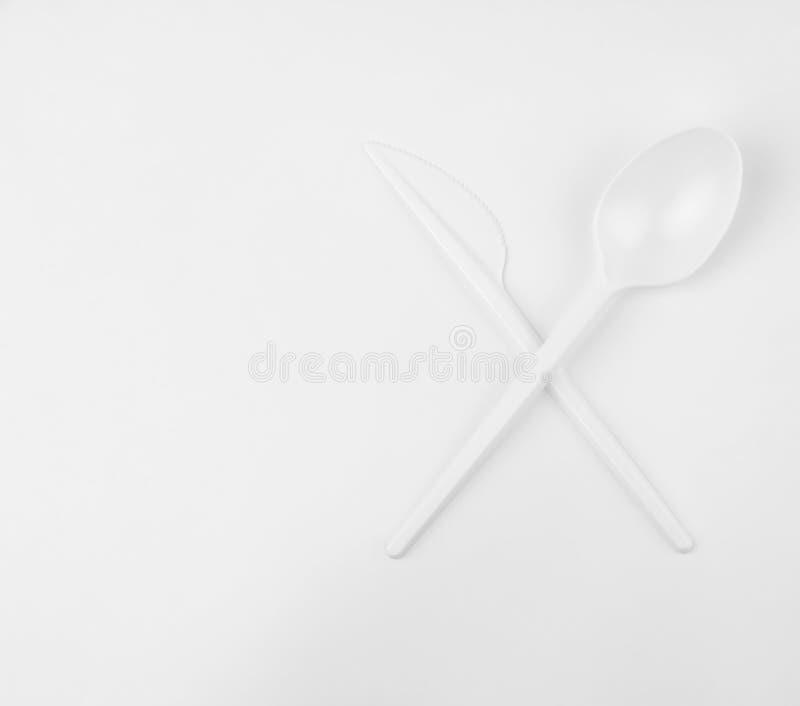 干净的白色塑料横渡的匙子和刀子在白色背景与拷贝空间,生态问题,特写镜头 免版税库存图片