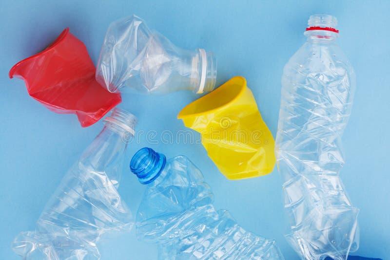 干净的被弄皱的塑料水瓶和五颜六色的红色和黄色一次性咖啡杯准备好在蓝色backg隔绝的回收 免版税库存照片