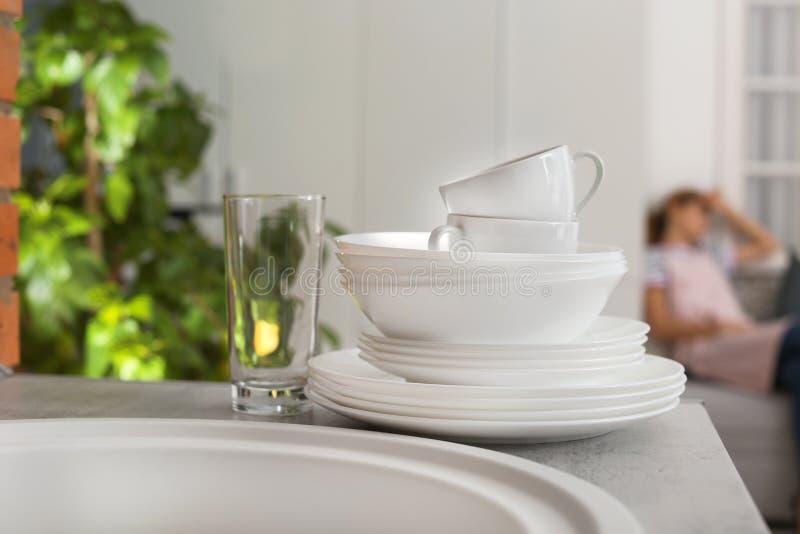 干净的餐具和疲乏的主妇妇女 库存图片