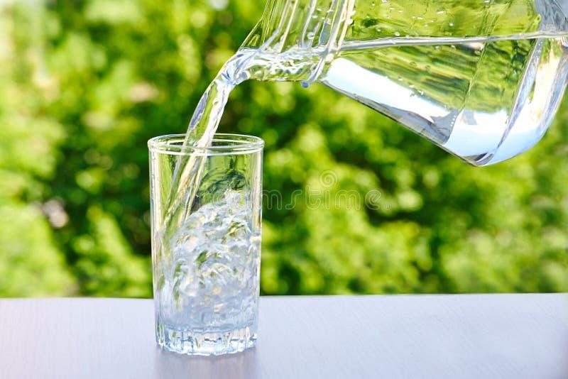 干净的饮用水从水罐倾吐入玻璃 库存图片