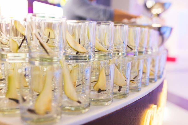 干净的玻璃行威士忌酒的由男服务员为饮料做准备,与切片的强的酒精新鲜的可口梨 库存图片