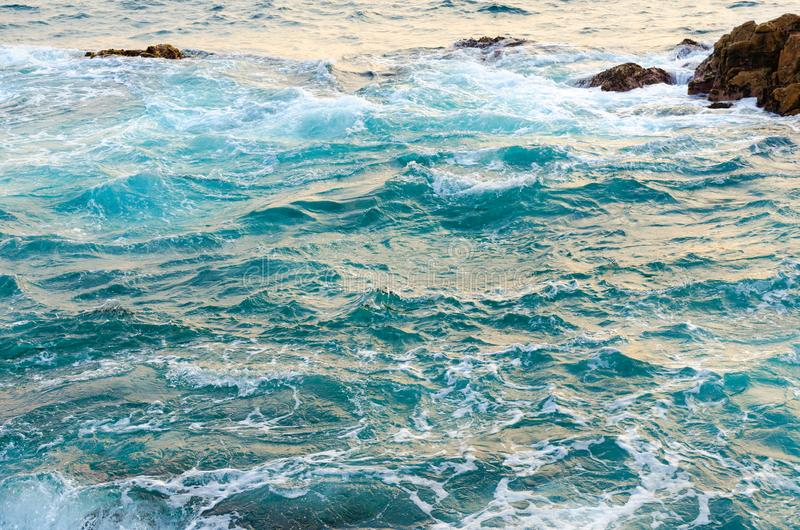 干净,清楚的海水击中石头、波浪和海滩,自然背景概念 免版税库存照片