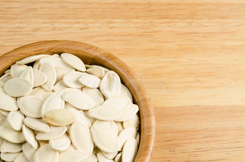 干南瓜籽,在木背景 免版税图库摄影