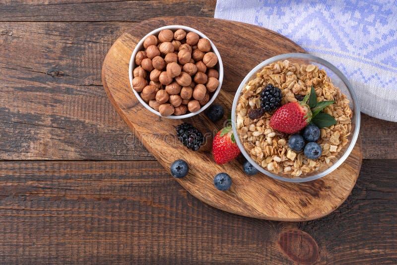 干和健康早餐用莓果和坚果在木背景 免版税库存图片