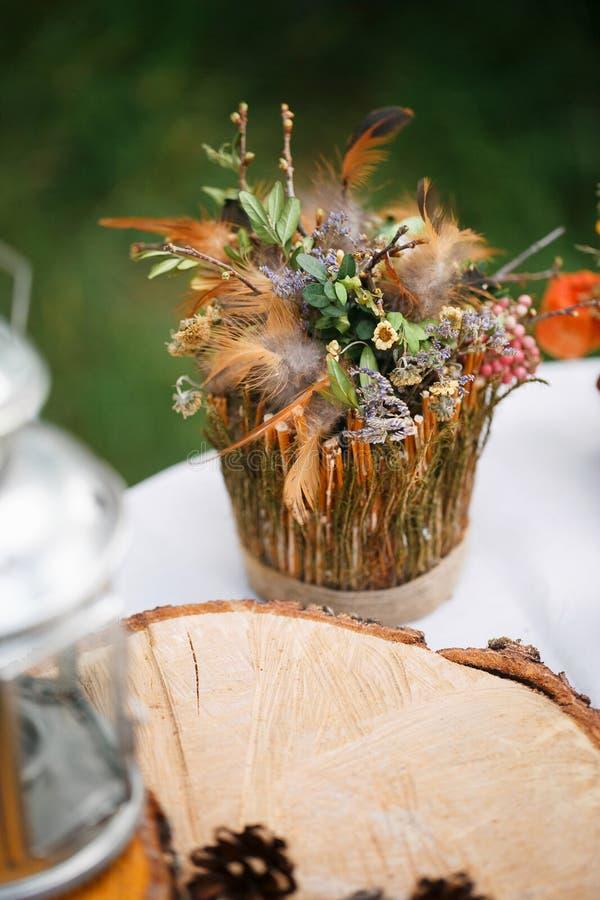 干小花、棕色羽毛和绿色叶子花束  在地球圈子的主角 图库摄影