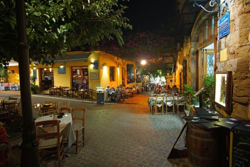 干尼亚州,克利特,10月01日2018游人各种各样的国籍在酒吧和餐馆放松城市的狭窄的街道的 库存图片