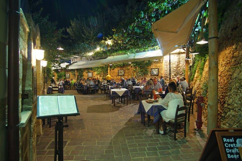 干尼亚州,克利特,10月01日2018游人各种各样的国籍在酒吧和餐馆放松城市的狭窄的街道的 免版税库存图片