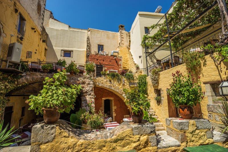 干尼亚州,希腊- 8月2017 :在午间期间的五颜六色的干尼亚州街道与地方礼品店和餐馆沿街道在C 库存图片