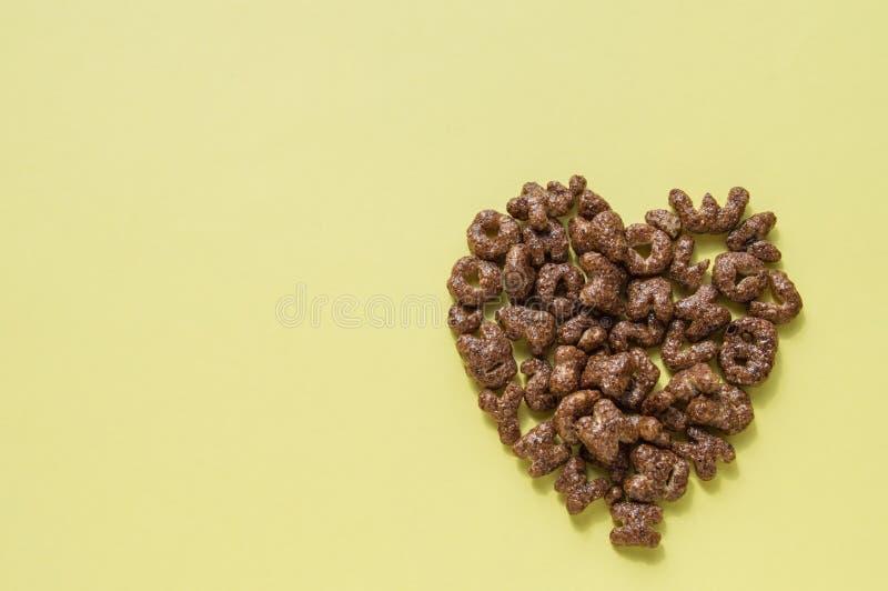 干早餐谷物的心脏的标志以字母表,巧克力的形式剥落孩子的有用的食物, 免版税库存照片