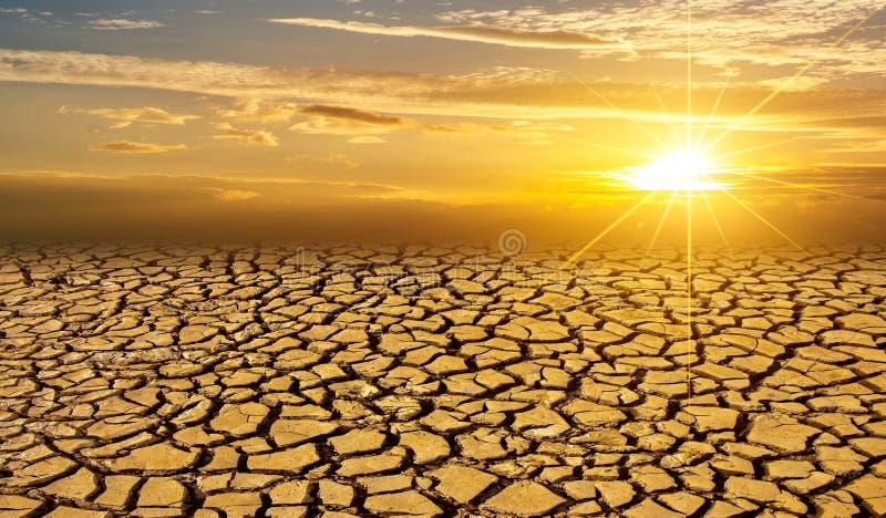干旱的粘土太阳沙漠全球性慢行的概念崩裂了被烧焦的地球土壤天旱沙漠风景剧烈的日落 免版税图库摄影