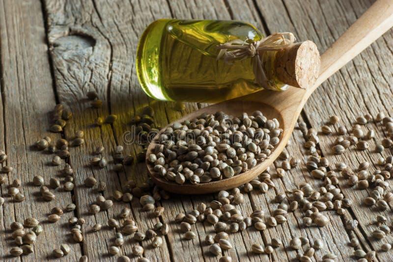 干有机大麻籽或大麻植物种子堆在匙子和碗有杯的大麻籽油 免版税库存照片