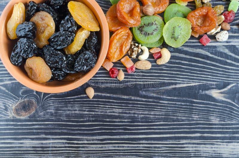 干李子在一个碗的杏干在一张黑暗的背景顶视图pl 库存图片