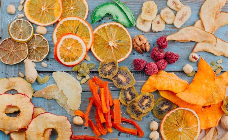 干果和菜芯片、糖煮的南瓜切片、坚果和种子在蓝色木背景 免版税库存照片