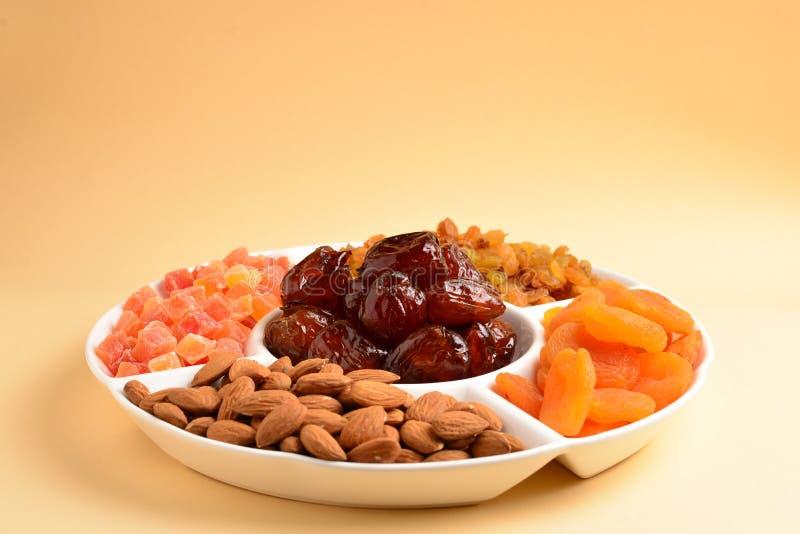 干果子和坚果的混合在一块白色板材 杏子,杏仁,葡萄干,约会果子 在米黄背景 文本的空间或 库存图片