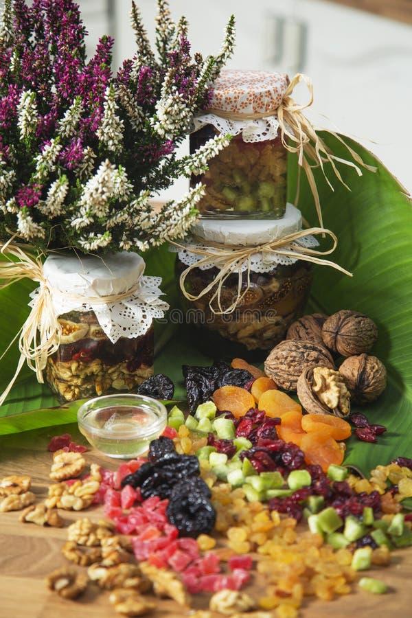 干果子和瓶子的安排蜂蜜果子混杂的人群 免版税库存图片