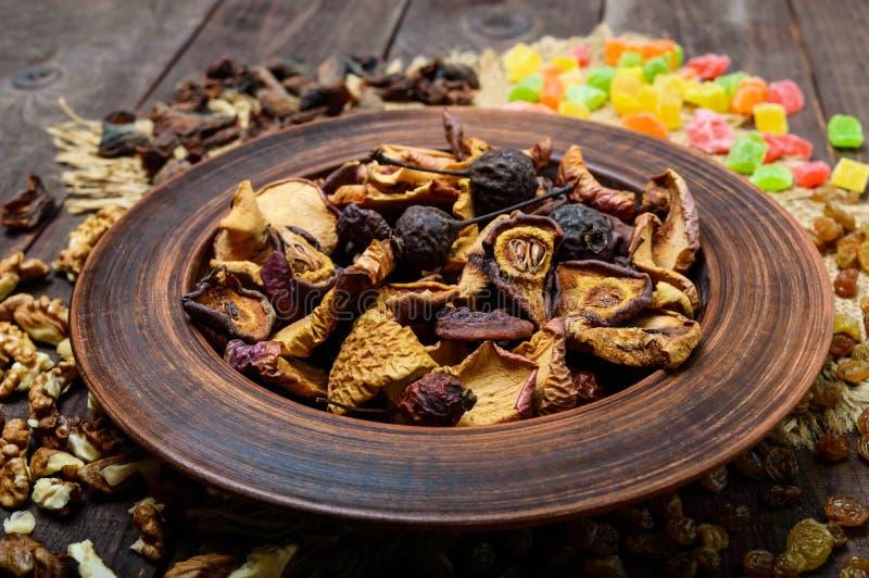 干果苹果、梨、杏子、莓果、葡萄干和坚果在一个碗在黑暗的木背景 免版税库存照片