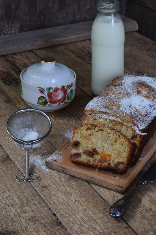 干果蛋糕用葡萄干,杏子,樱桃 圣诞节的酥皮点心 被切的新近地被烘烤的水果蛋糕和牛奶 早餐或以后 免版税库存图片