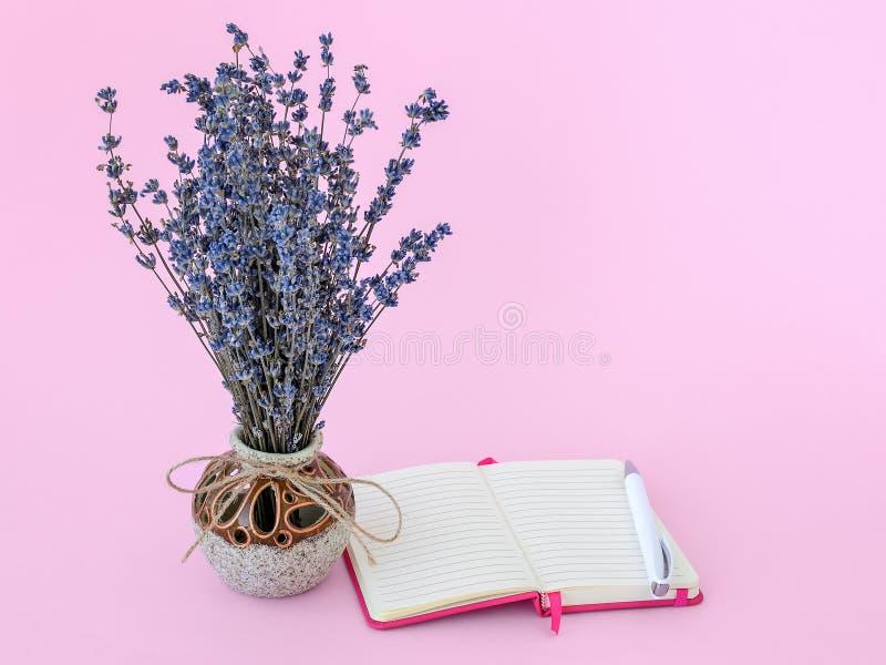 干淡紫色芬芳花束与小紫色花的在纸笔记薄附近的一支美丽的陶瓷花瓶和圆珠笔 库存照片