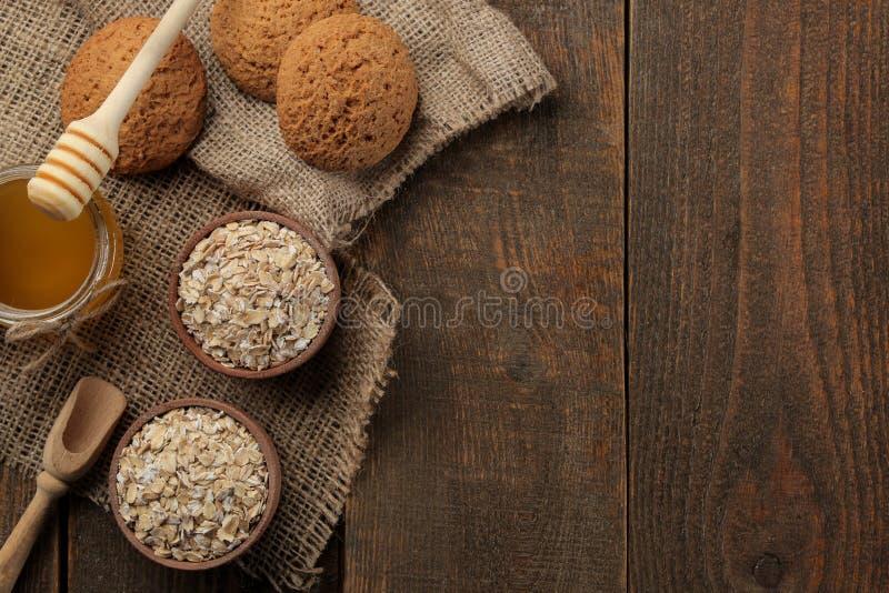 干燕麦粥、蜂蜜和麦甜饼 食物 健康的食物 在一张棕色木桌上 与空间的顶视图题字的 免版税图库摄影