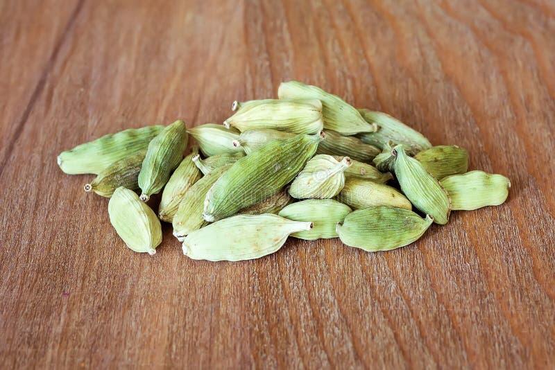 干燥豆蔻果实种子堆在一个棕色木切板的 自然食物香料和调味料 鲜美吃 免版税库存照片