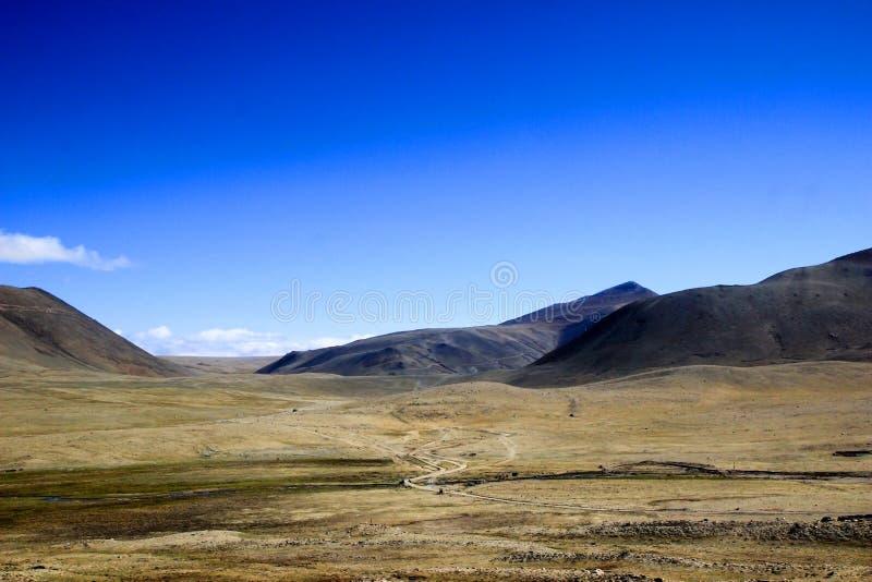 干燥贫瘠沙漠土地的宽全景有路山和天空蔚蓝的 免版税图库摄影