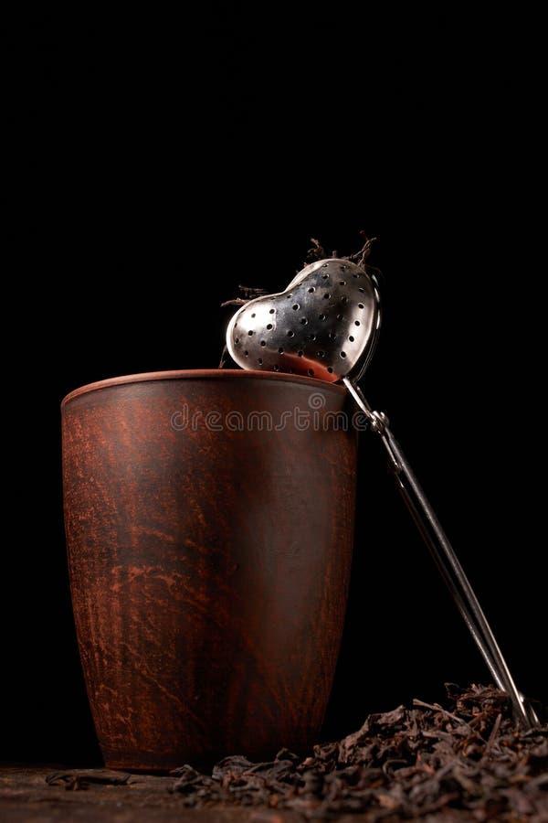 干燥黑中国茶具,与过滤器特写镜头、杯子和茶壶在背景在老木委员会 免版税库存图片