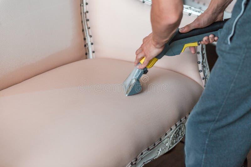 干燥cleaner& x27;s雇员手专业地清洗古典沙发与提取方法 库存照片