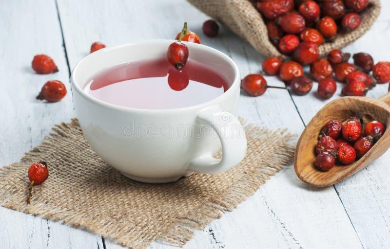 干玫瑰果杯子在白色黑木桌上的清凉茶药用植物与木铁锹和野玫瑰果在粗麻布大袋 Dogr 免版税库存图片