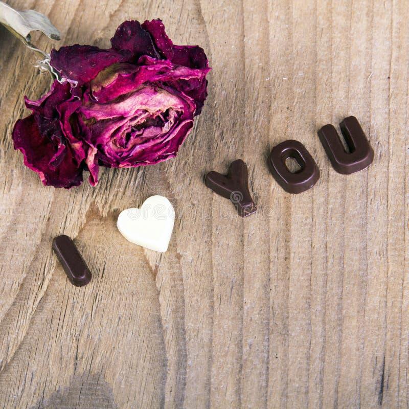 干玫瑰色和巧克力词我爱你 库存图片