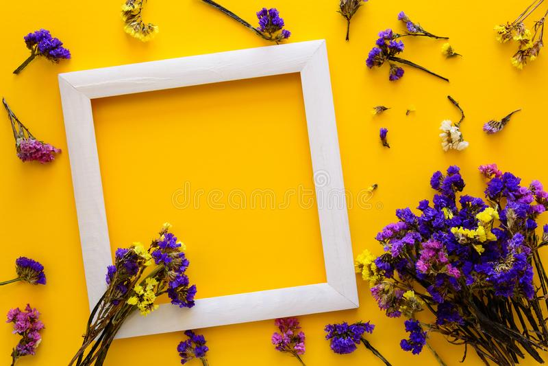 干秋天五颜六色的花束开花说谎在黄色纸背景的一个白色框架 复制空间 平的位置 顶视图 免版税库存照片