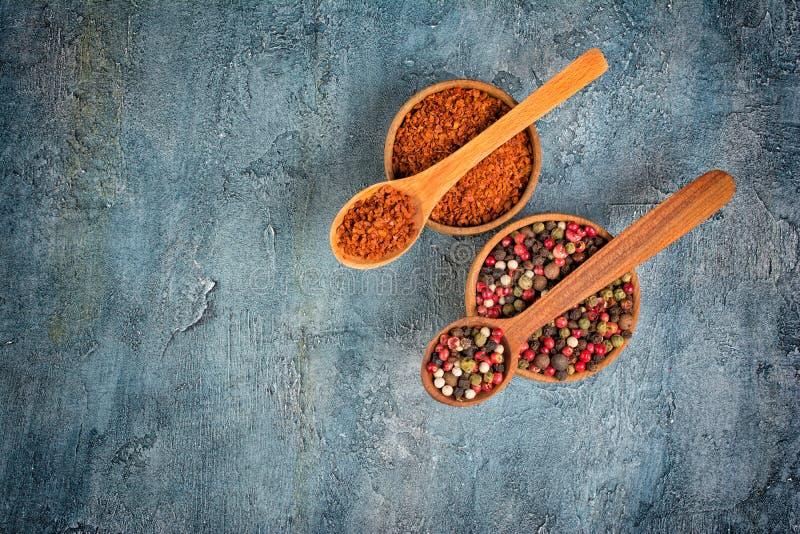 干红色辣椒和混合胡椒顶视图在木碗和匙子 图库摄影