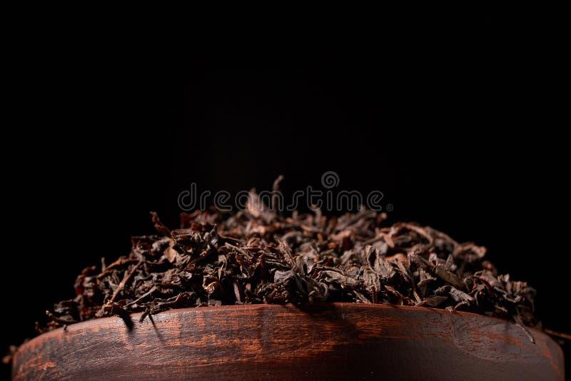干红茶顶视图在黏土碗的在木桌上 茶生产的概念 宏指令,关闭 库存照片