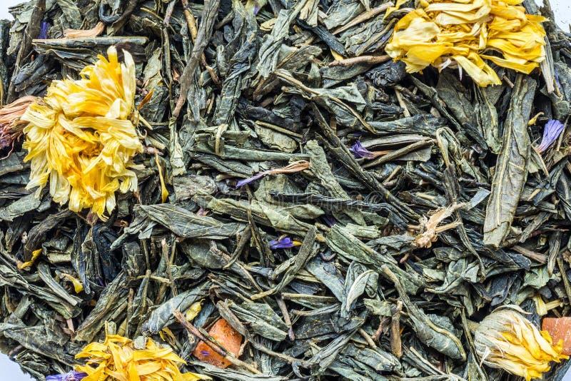 干绿茶,草本成份饮料抽象背景纹理与金盏草花的 免版税库存图片