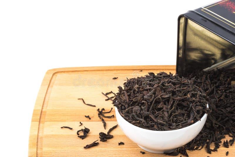 干茶涌入在一个木板的一个陶瓷杯子在白色背景 库存照片
