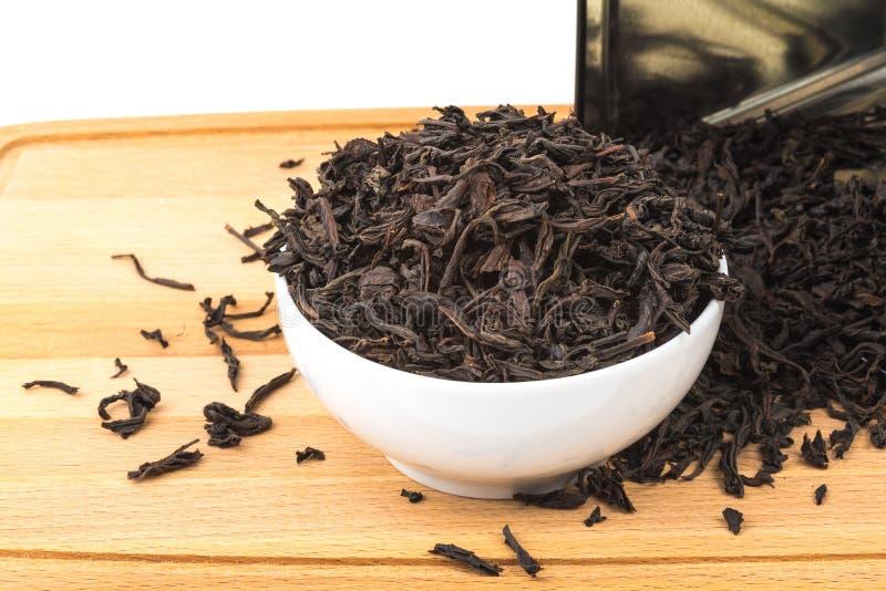 干茶涌入在一个木板的一个陶瓷杯子在白色背景 免版税库存图片