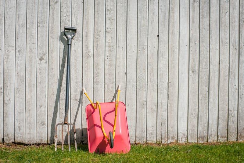 干草叉和一辆独轮车在庭院里 库存图片