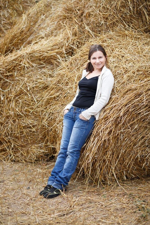 干草堆背景的妇女  免版税图库摄影