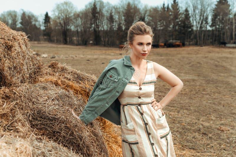干草棚附近自然中的美丽女人 免版税库存照片