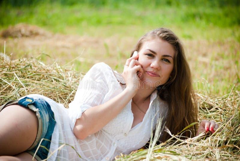 干草的美丽的妇女谈话在手机 免版税图库摄影