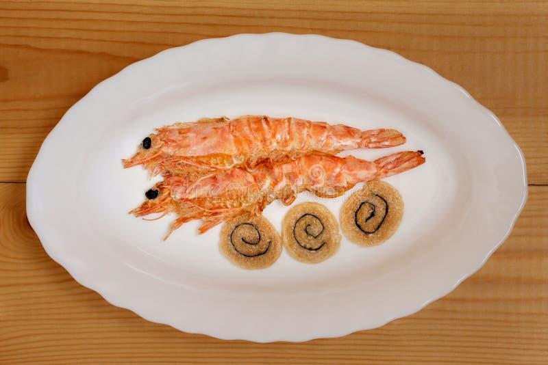 干虾用在一块白色板材的饼干 免版税库存图片