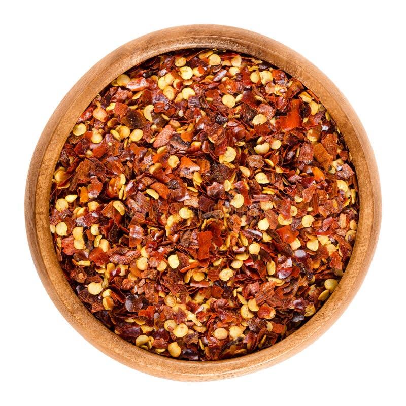 干辣椒在白色的木碗剥落 免版税图库摄影