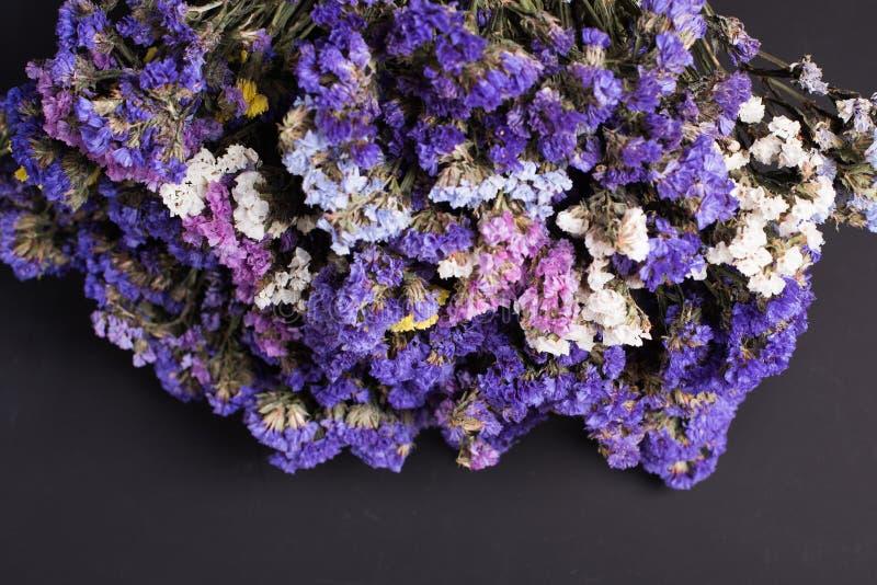 干野花花束在葡萄酒木板条的顶视图黑纹理背景的水平 库存照片