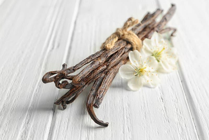 干香草棍子和花在轻的木背景 免版税库存照片