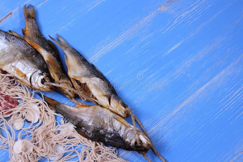 干rudd鱼和捕鱼网在蓝色背景 图库摄影
