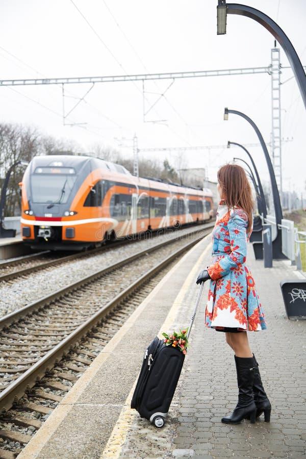 平台和火车的妇女 免版税库存图片